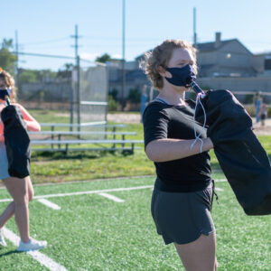 Amanda Dowdican (left) and Lauren Sharp (right) practice marching positions at a student organized rehearsal on Elbel Field. Image credit: Eric Bronson/Michigan Photography