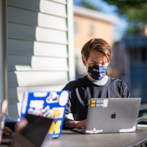 Clarinet section leader Michael Grasinski takes virtual marching band classes from the front porch of his house. Image credit: Eric Bronson/Michigan Photography