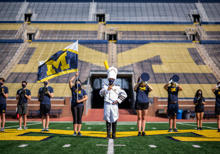 A small number of Michigan Marching Band members pose at the empty Michigan Stadium during a photoshoot. Image credit: Eric Bronson/Michigan Photography