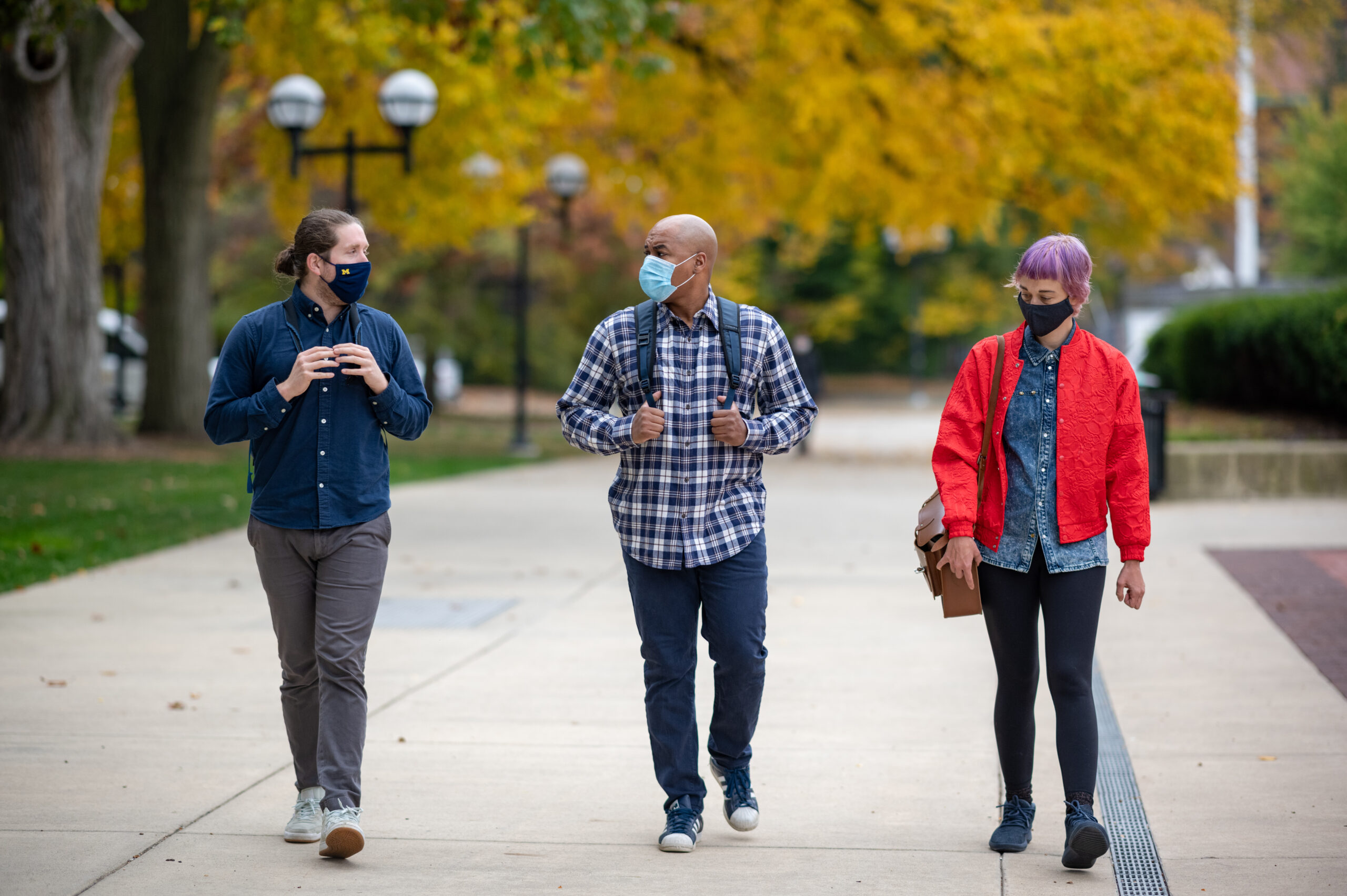 University of Michigan School of Information graduate students Joshua Tooker, Michael Payne and Lauren Trimble, (left to right) walk on campus. Image credit: Eric Bronson, Michigan Photography