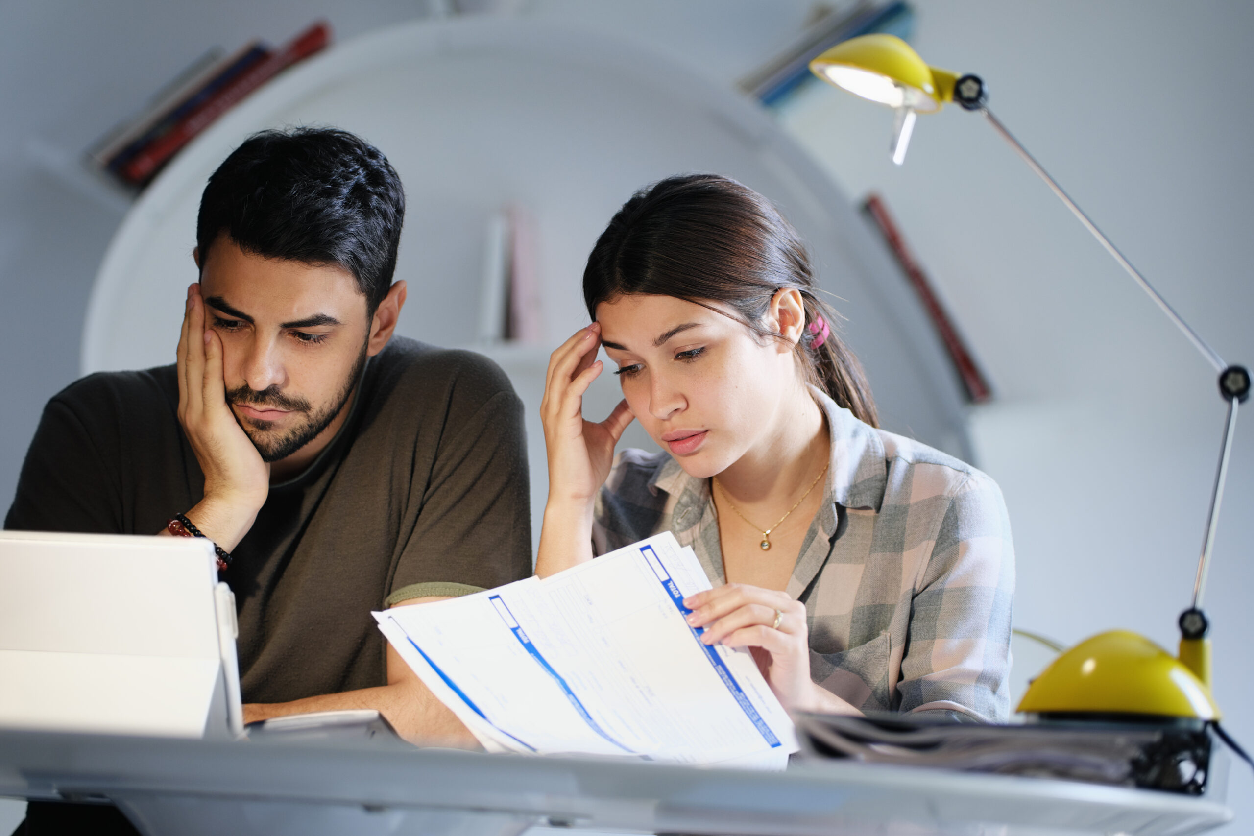 Young couple reviewing invoices and doing family business plan. Concept of money and economic problem for man and woman living together. Image credit: iStock
