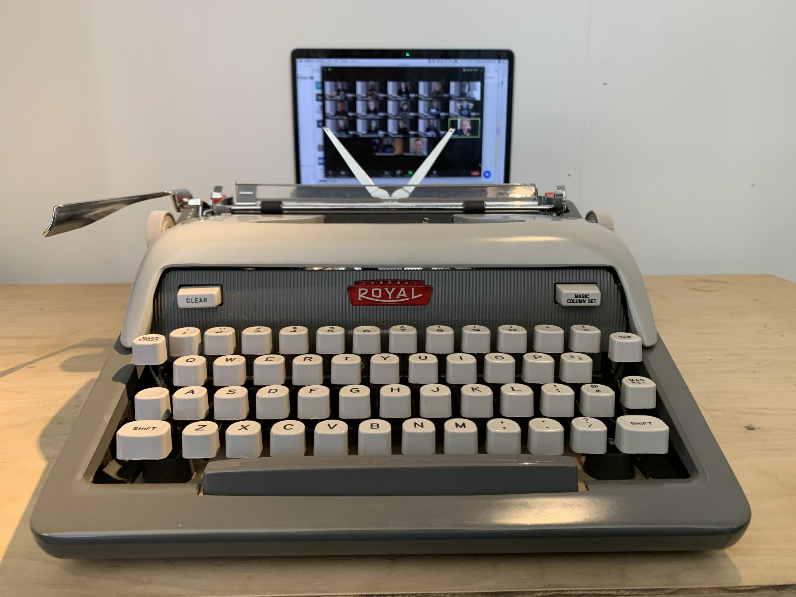 Typewriter with computer in background on zoom call.