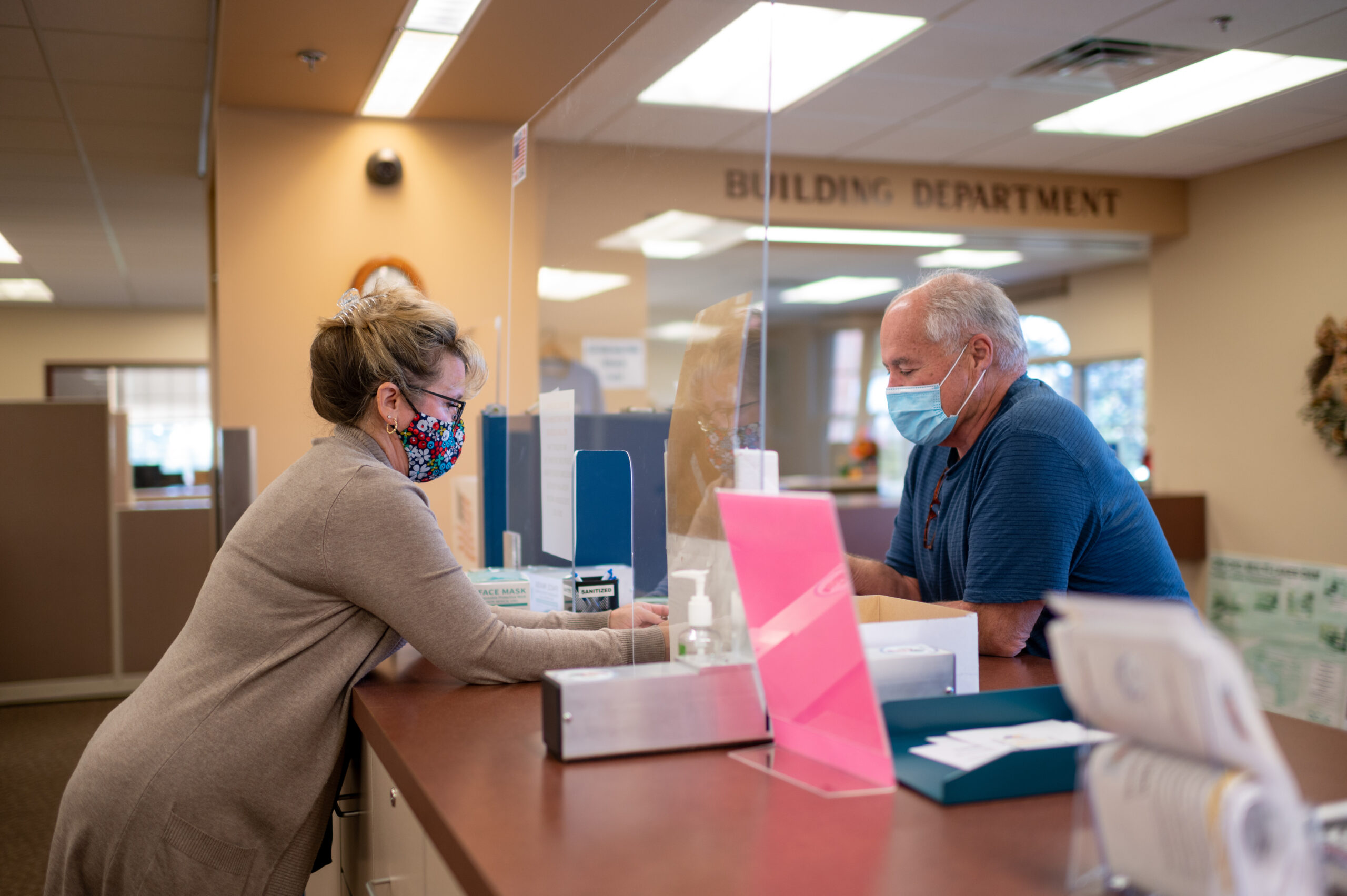 Kelly Richter, the clerk's office administrative assistant in Oxford Township, assists a resident at the public counter. Image credit: Eric Bronson, Michigan Photography