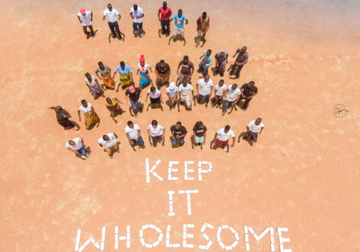 "Community gathered around ""Keep it Wholesome"" sign."
