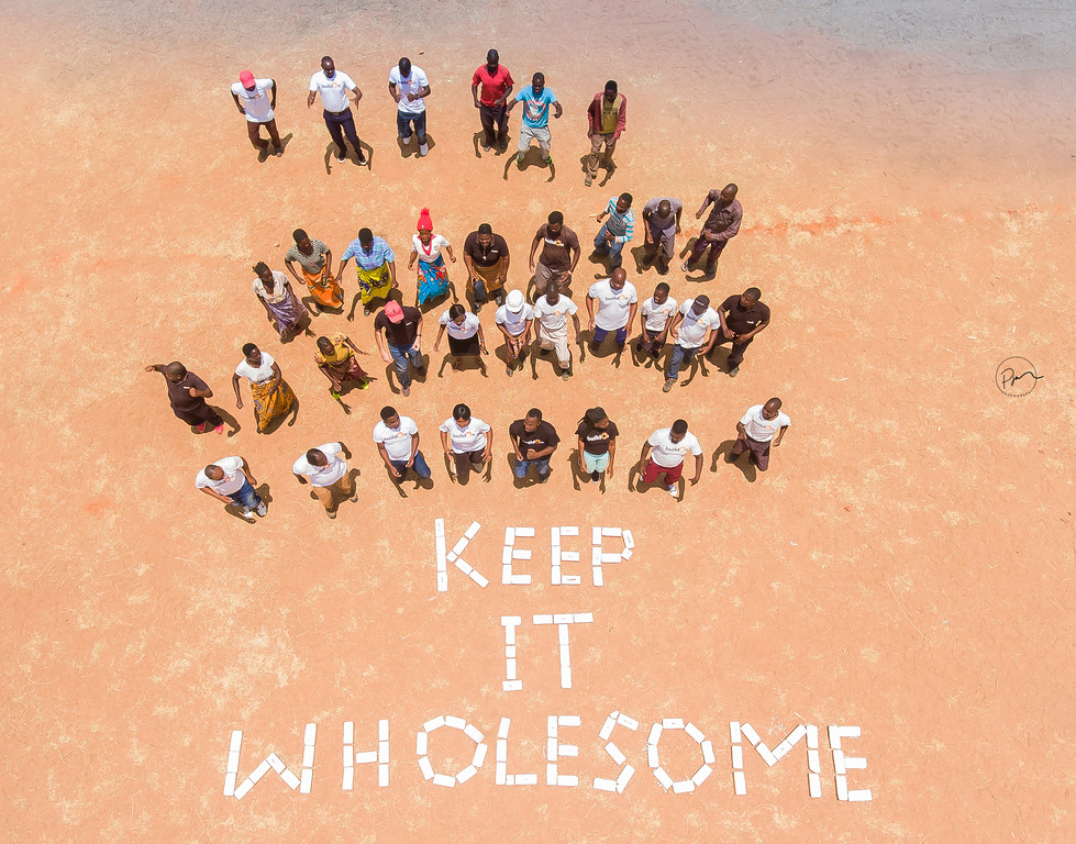 """Community gathered around """"Keep it Wholesome"""" sign."""