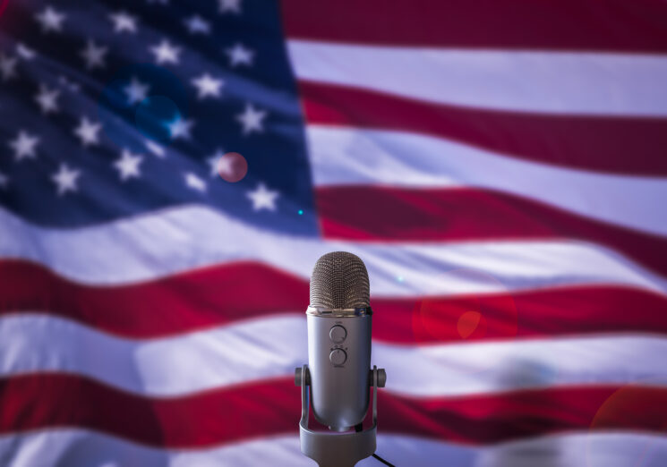 A Microphone In Front Of A USA Flag. Image credit: iStock