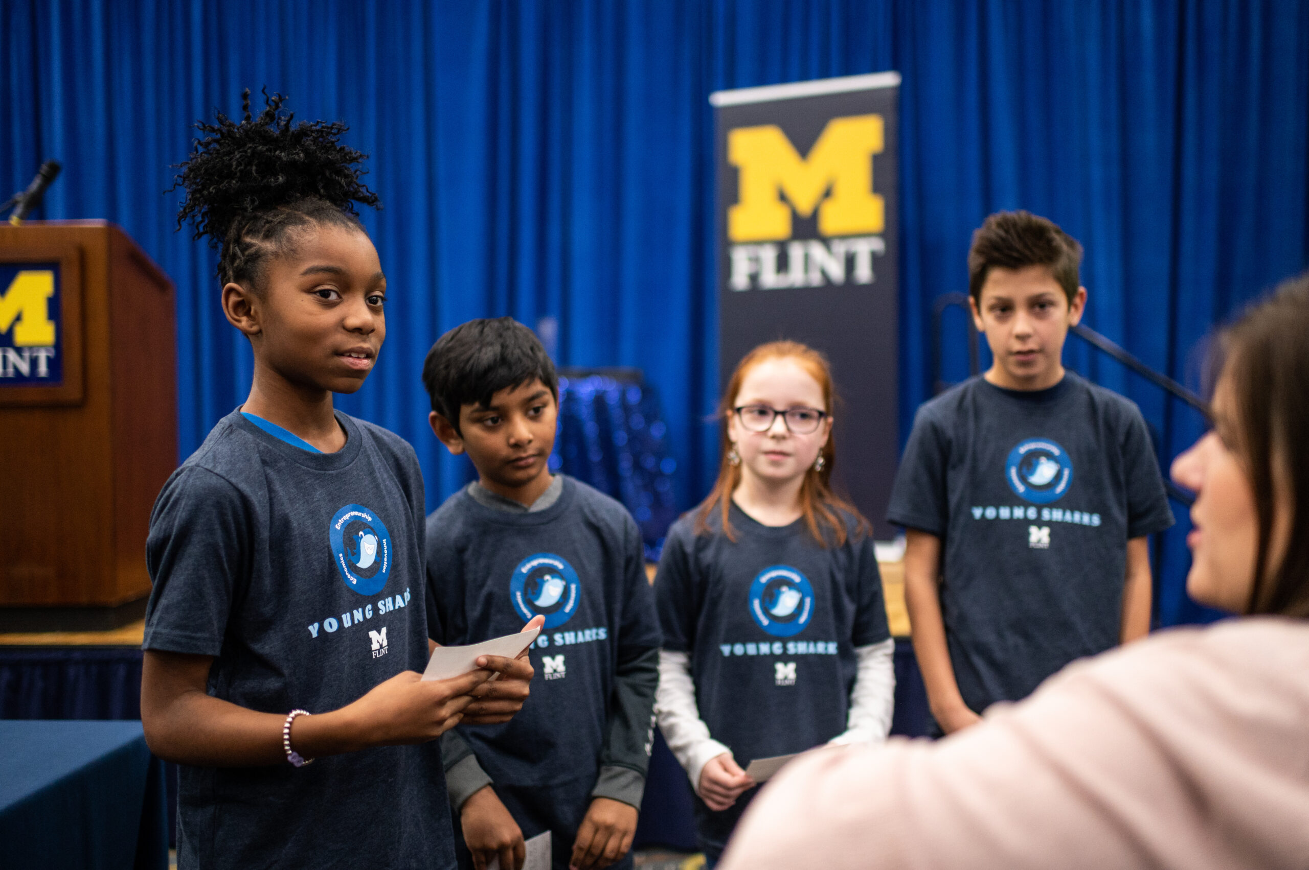 Students from Mason Elementary School of Grand Blanc Community Schools discuss their presentation strategy with their teacher during the presentation on 12/3/2019 at Riverfront Banquet Center on the UM-Flint campus. Image credit: Eric Bronson / Michigan Photography