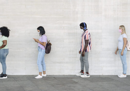 Young people of different races in line 6 ft apart due to COVID-19. Image credit: iStock