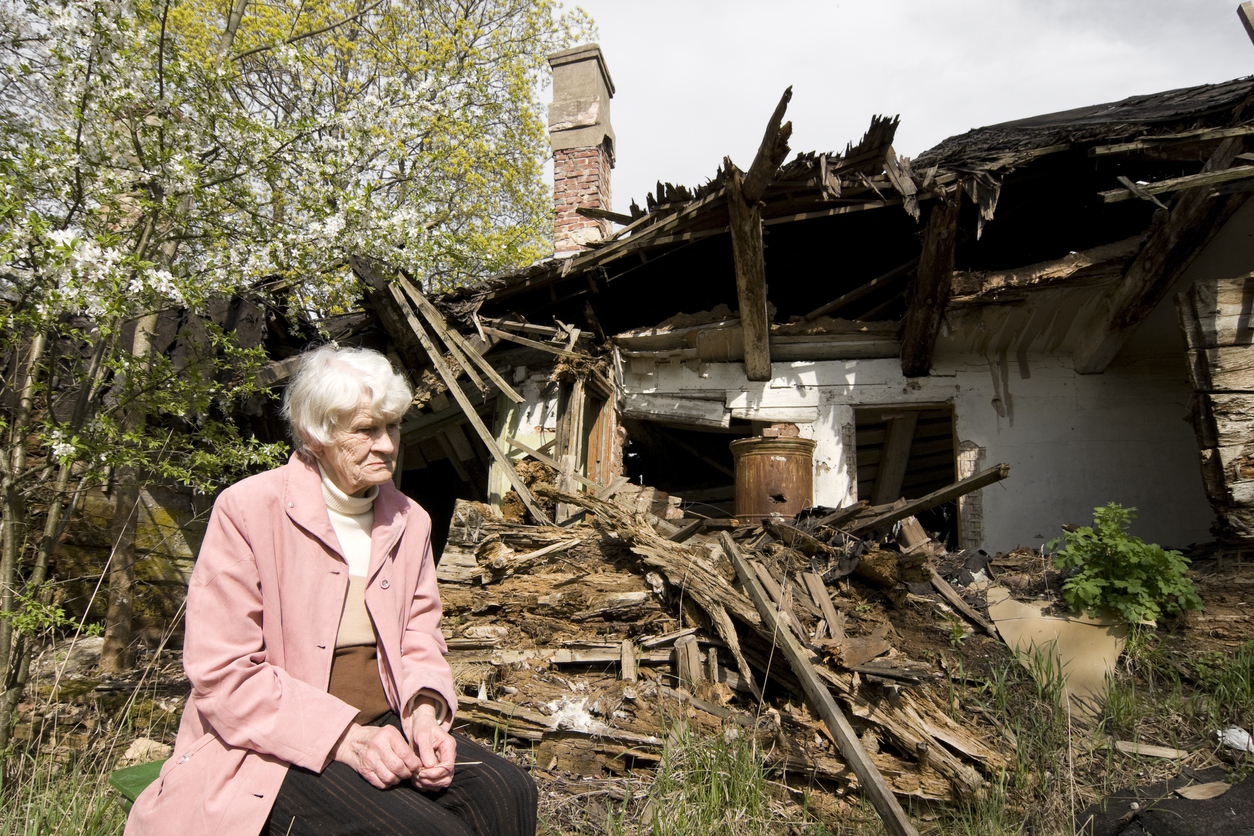 A senior citizen sits outside a destroyed home. Image credit: iStock
