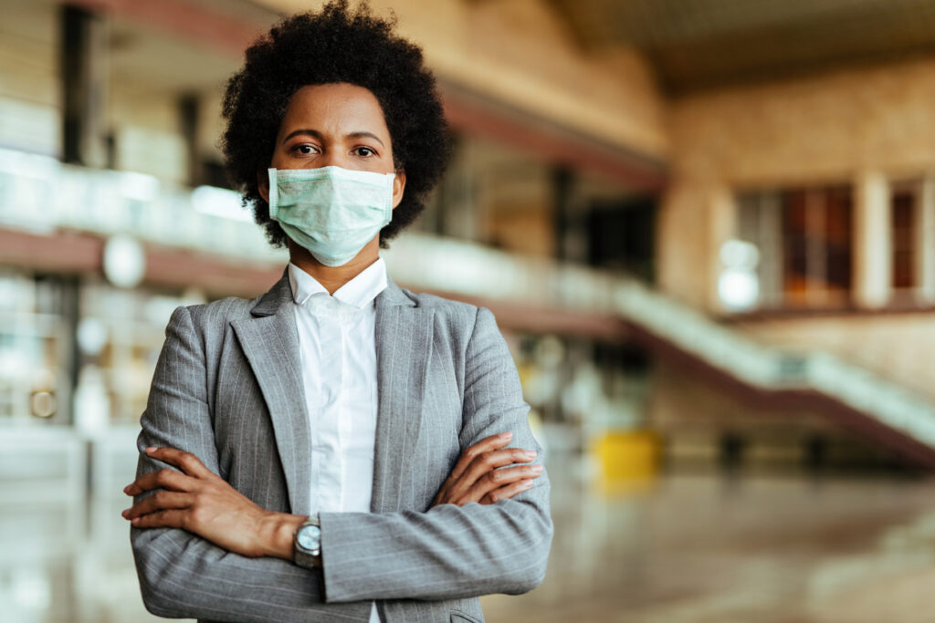 A Black woman wearing a suit and face mask. Image credit: iStock
