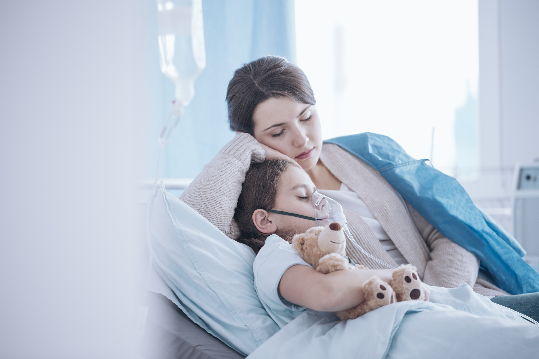 Mother taking care of sick daughter with oxygen mask and teddy bear. Image credit: iStock