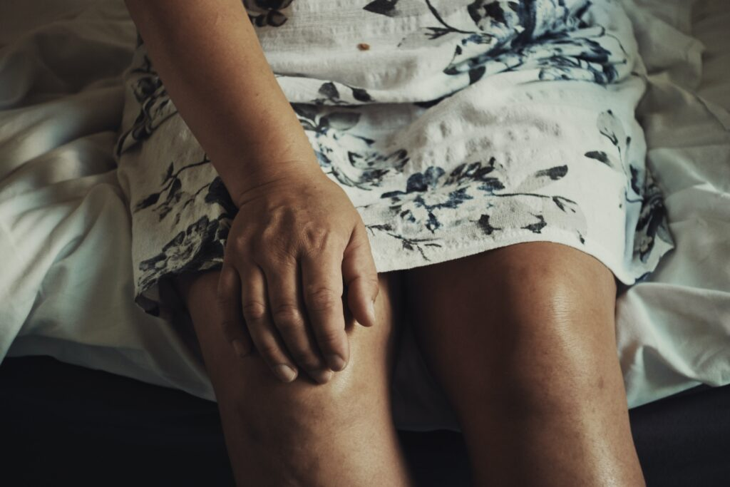 A woman's hand on her knee. Image credit: Anna Auza on Unsplash