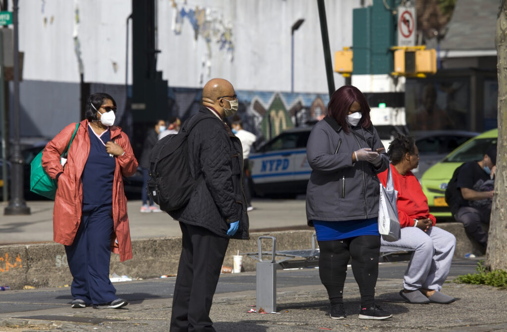 People wait for bus while wearing masks during COVID-19 Bronx NY. Image credit: eddtoro, iStock