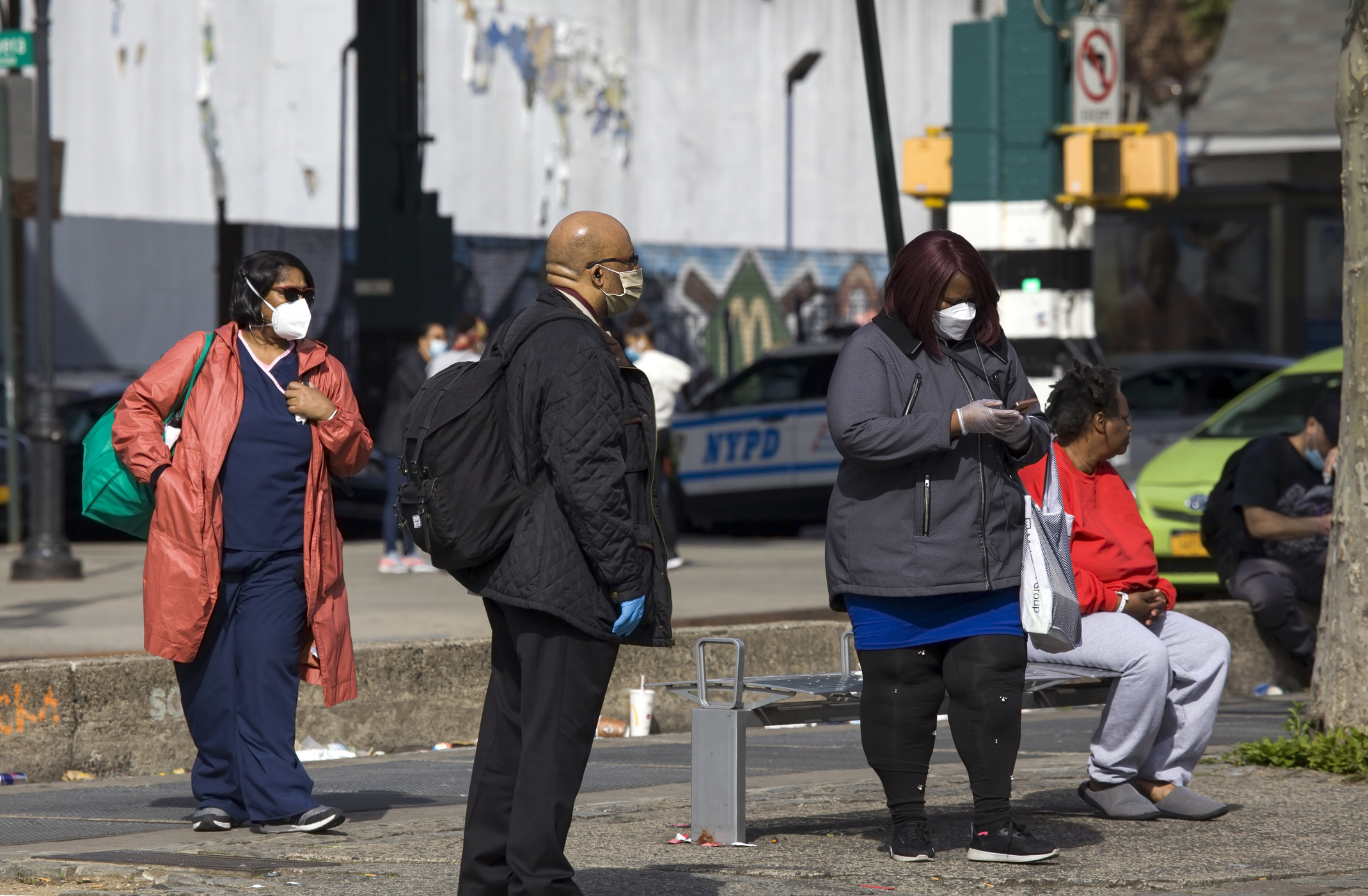 People wait for bus while wearing masks during COVID-19 Bronx NY. Image credit: eddtoro, iStock