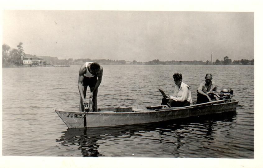 Black and white photo of three men on a boat fishing.