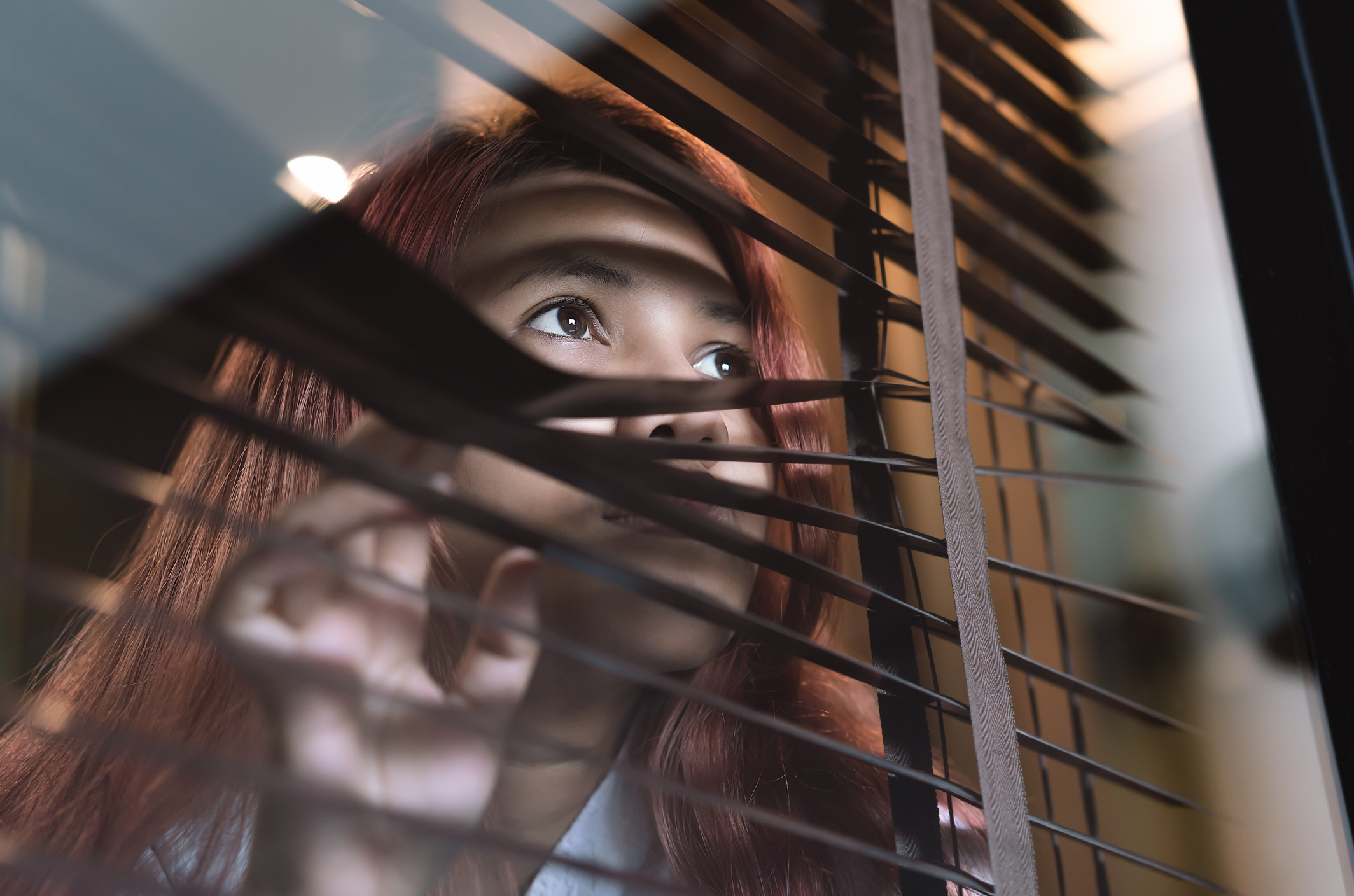 Asian woman looking through window blinds spying on neighbours - Young lonely millennial woman peeping through glass observing gossip and action outdoors - introvert, spy and intrusive concepts. Image credit: iStock