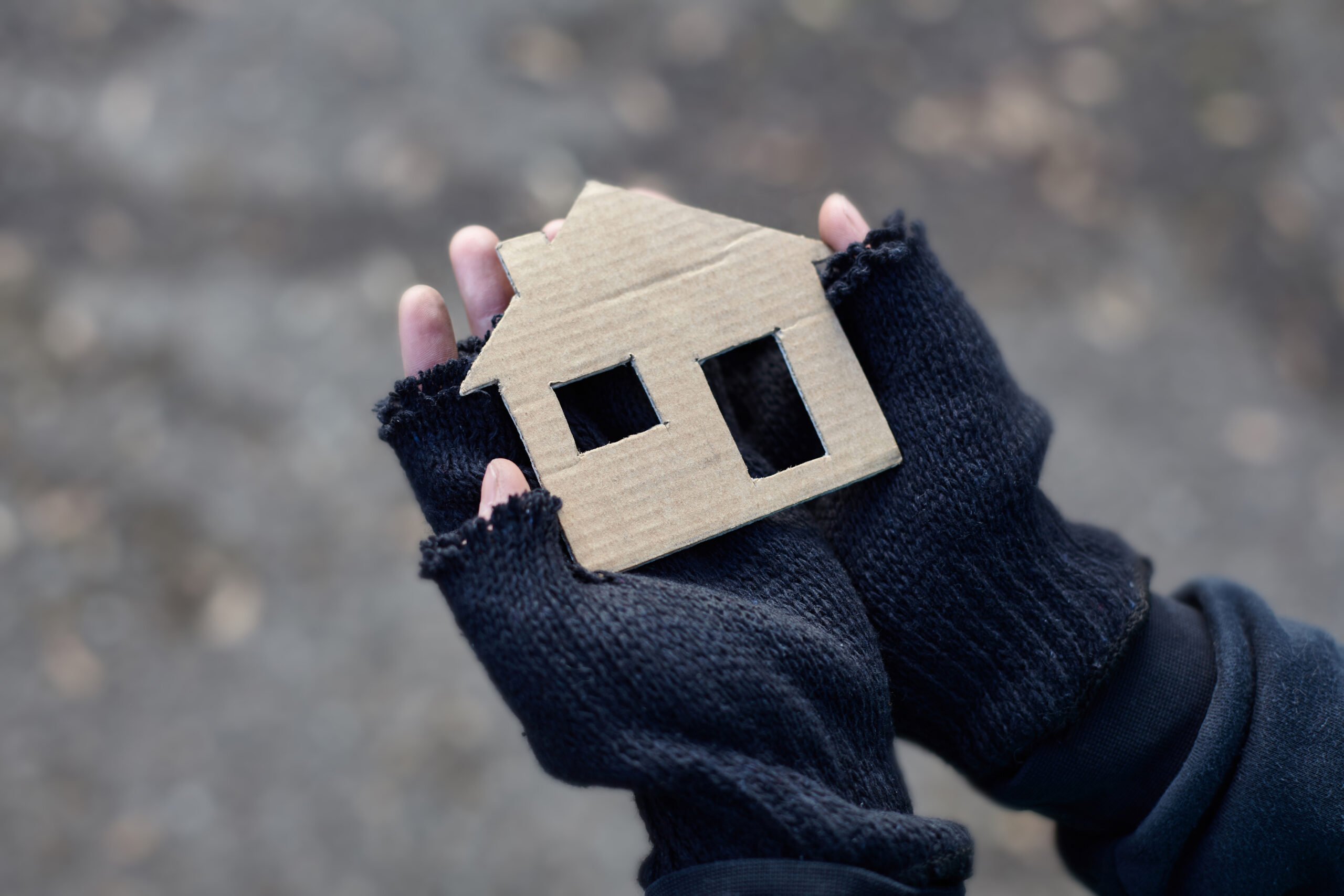 young homeless boy holding a cardboard house. Image credit: iStock