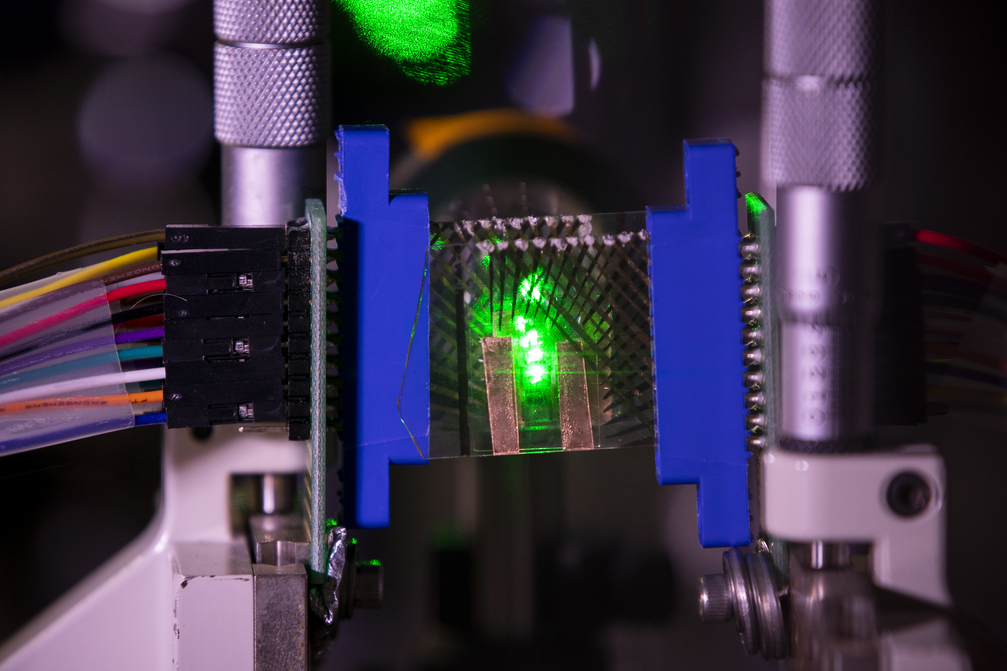 A graphene-based transparent photodetector array (acting as two layers of sensors in a camera) measures the focal stack images of a point object simulated by focusing a green laser beam onto a small spot in front of the lens inside Ted Norris' lab on North Campus in Ann Arbor, MI on January 27, 2021. Norris and his team fabricated a prototype of transparent photodetector arrays with graphene on glass and used two pieces of the detector arrays separated slightly apart and behind an imaging lens to demonstrate its potential applications in 3D object tracking tasks. With this prototype's application this will aid in autonomous driving and robotics, responding to moving objects that require their perception units to obtain not only what they are but also where and how far they are in real time. Image credit: Robert Coelius/Michigan Engineering, Communications and Marketing