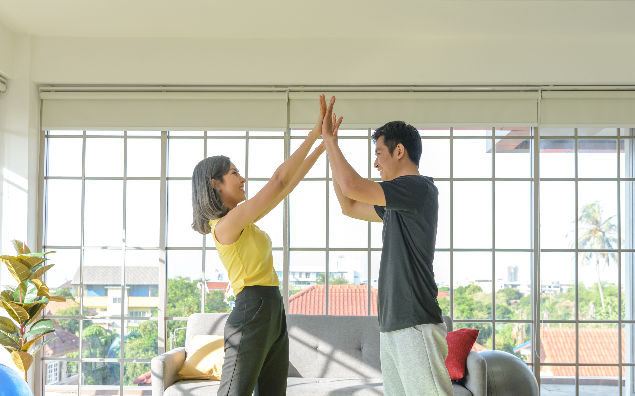 Young asian couple wear casual clothing giving high five to each other and smiling in liveing room. Image credit: Pratchaya, iStock.