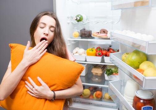Woman with a pillow next to a refrigerator stock with fruits and veggies. Image credit: iStock