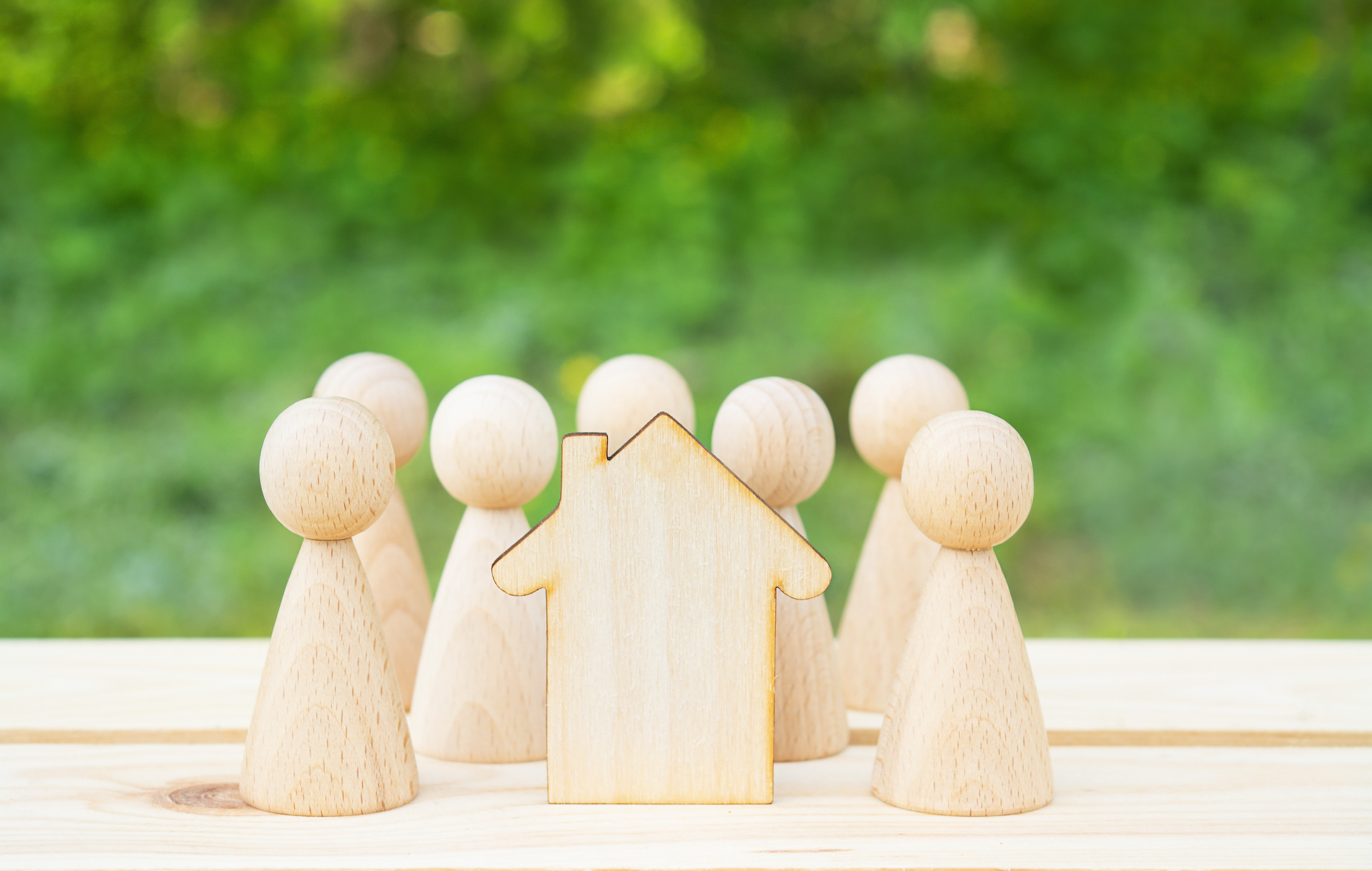 Family concept. Wooden house and many little men on a wooden table. Property division. Image credit: Yulia Romashko, iStock