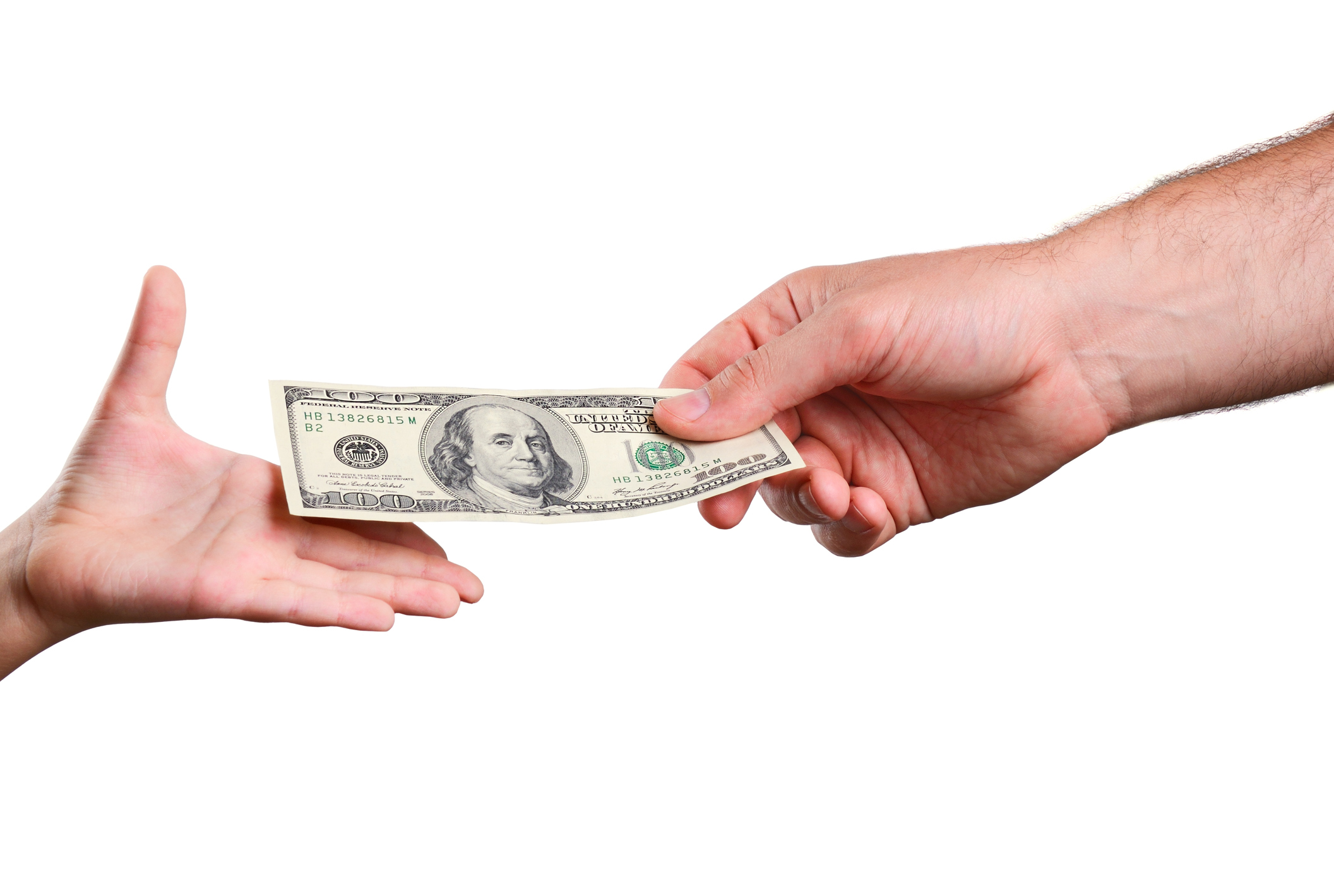 man's hand gives a the bill 100 US dollars in a child's hand. isolated on white background. horizontal. Image credit: TanyaRu, iStock