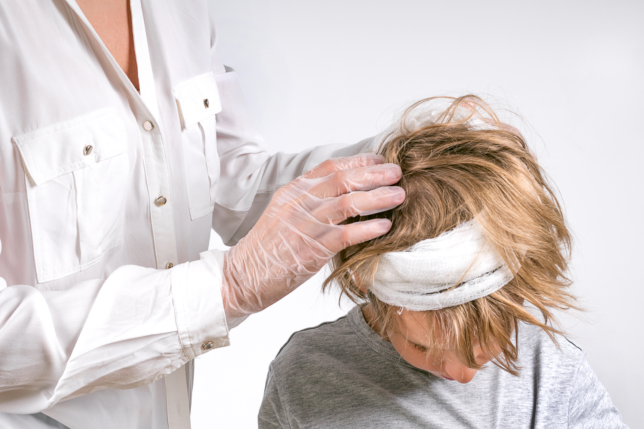 A doctor examines a young boy's head. Image credit: iStock