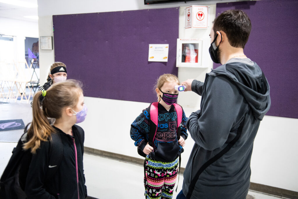 Three young kids get temperature checked by adult.