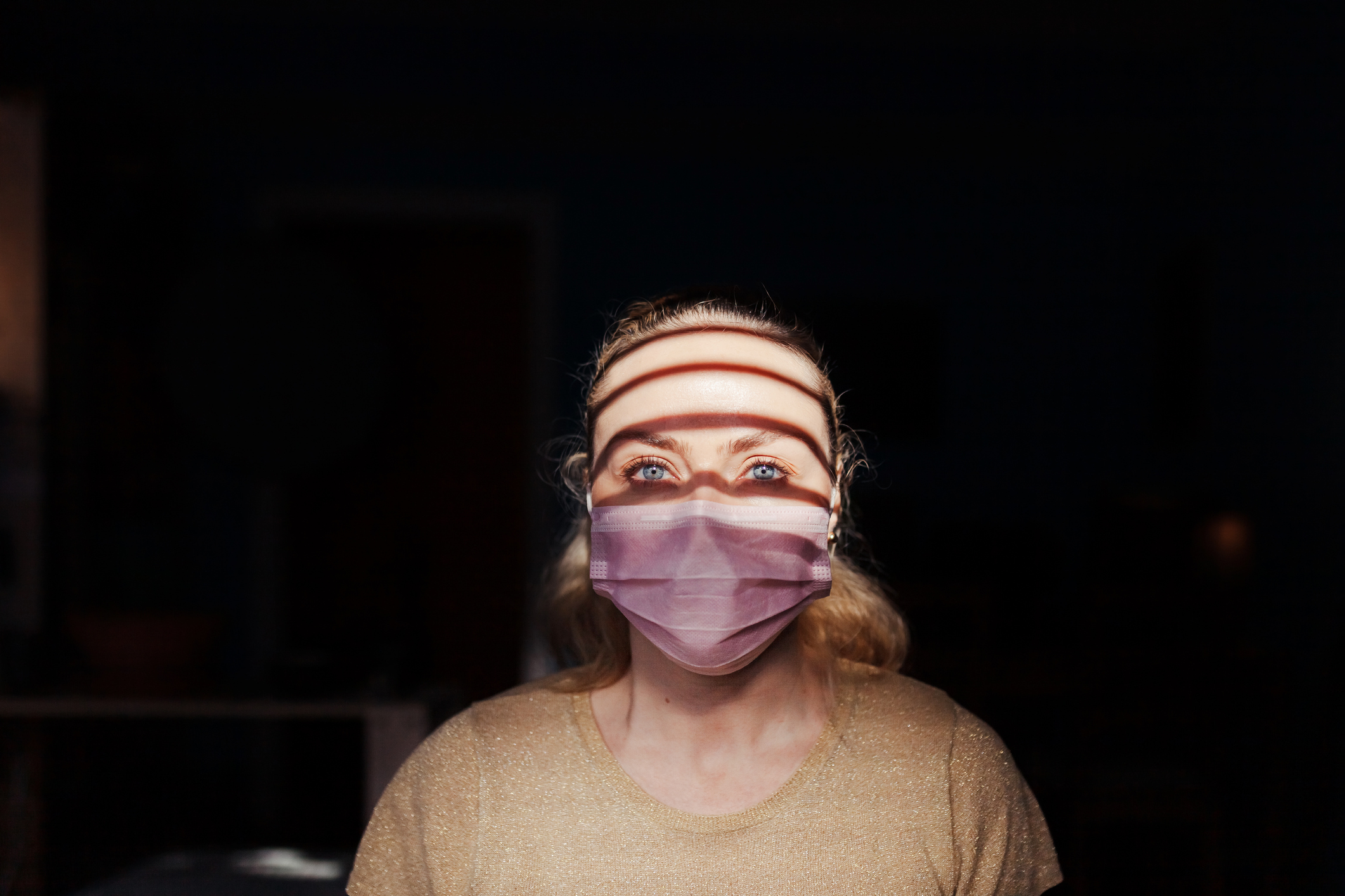 Woman wearing a surgical mask during quarantine in her house. Image credit: Manu Reyes, iStock