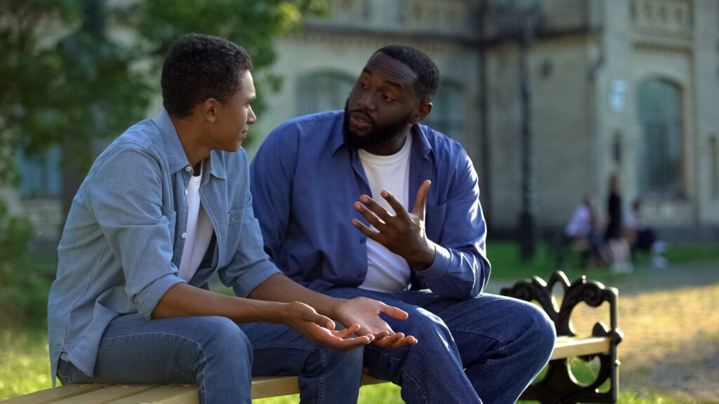 A Black father and son in conversation. Image credit: iStock