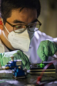 Changyeong Jeong, PhD Candidate in Electrical and Computer Engineering, handles an ultrathin Ag film based OLED inside Professor Jay Guo's lab at 3537 G.G. Brown on North Campus in Ann Arbor MI on May 5, 2021. Guo's group is systematically improving the light power distribution in OLEDs by removing the waveguide mode and optimizing the organic stacks and the ultrathin AG anode. This simple yet effective method leads to significantly enhanced performance of the external quantum efficiency of the OLED. Jeong and Guo's solution is not only simple in process but also can achieve high throughput and low cost with excellent compatibility with the large-scale manufacturing process in the display industry. In principle, the modal elimination approach introduced in this work could be extended to other solid-state light emitting diodes (LEDs) such as perovskites, quantum-dots, or III-V based LEDs since all of which are susceptible to the issue of light trapping as waveguide mode. Image credit: Robert Coelius/University of Michigan Engineering, Communications & Marketing