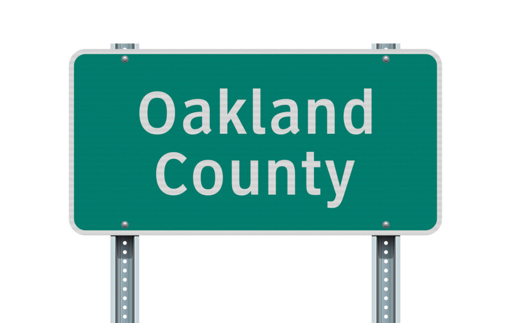 Vector illustration of the Oakland County green road sign on metallic posts. Image credit: Thomas Pajot, iStock
