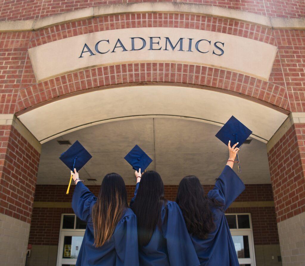 Female graduates raise hats at building sign. Image credit: Leon Wu, Unsplash