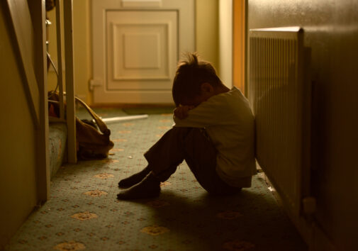 sad child with his head between his legs left alone at home. image credit: iStock