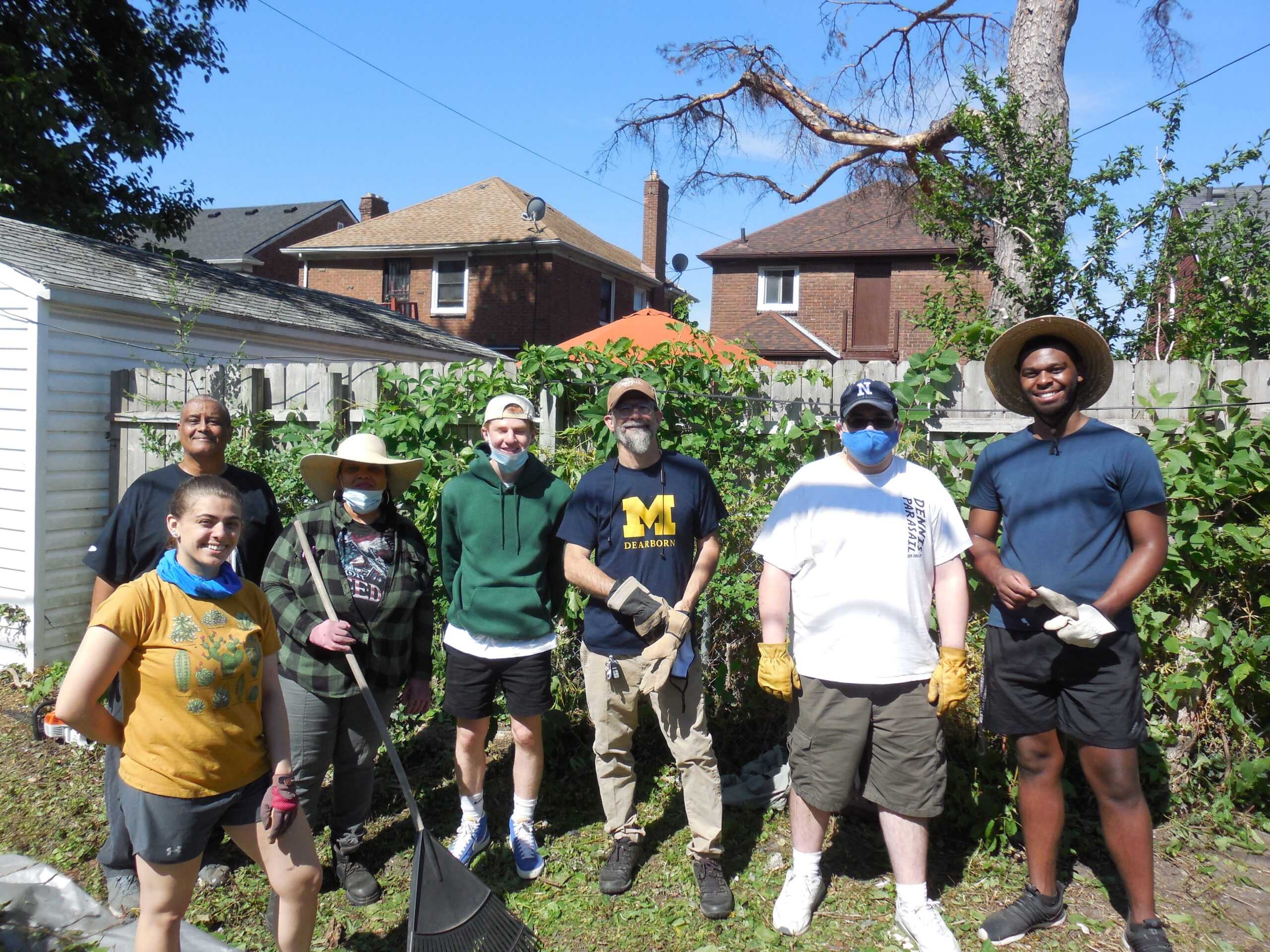 """Alley cleanup in the west McNichols area. Pictured (left to right): Amina Mikula, UM-Dearborn student, Robert Turner, resident, Anne Peeples, resident, Solomon Draus, UD-Jesuit student, Charles """"Chuck"""" Rivers, resident and president of the Neighborhood Association, Peyton Lynch, UM-Dearborn student, and Jacques Jones, UM-Dearborn student. Image courtesy: Paul Draus"""
