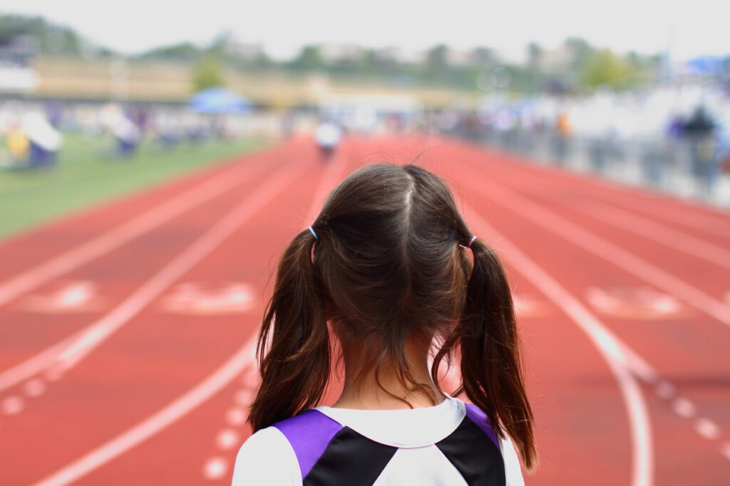 A young girl looks at a race track. Image credit: iStock