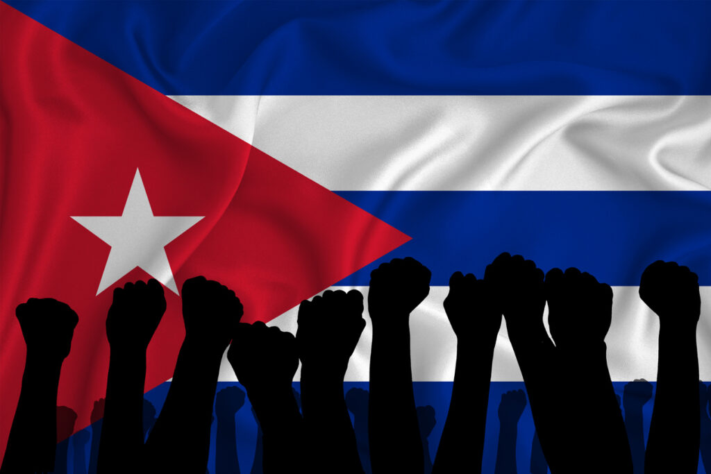 Cuban flag with protestors. Image credit: iStock