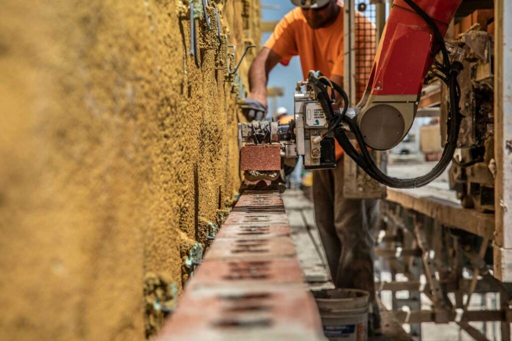 Barton Malow already uses simple robots on some job sites, such as the Semi-Automated Mason, which mortars and places bricks in the exterior walls of large buildings. The firm is a collaborator on a $2M, U-M led project that aims to enable robots to learn from and cooperate with human construction workers. Image credit: Construction Robotics