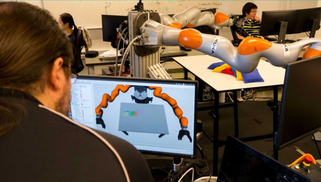 A U-M graduate student operates a KUKA robot similar to the ones used in Carol Menassa's robot apprentice research. The $2M project aims to enable robots to learn from and cooperate with human construction workers. Image credit: Robert Coelius