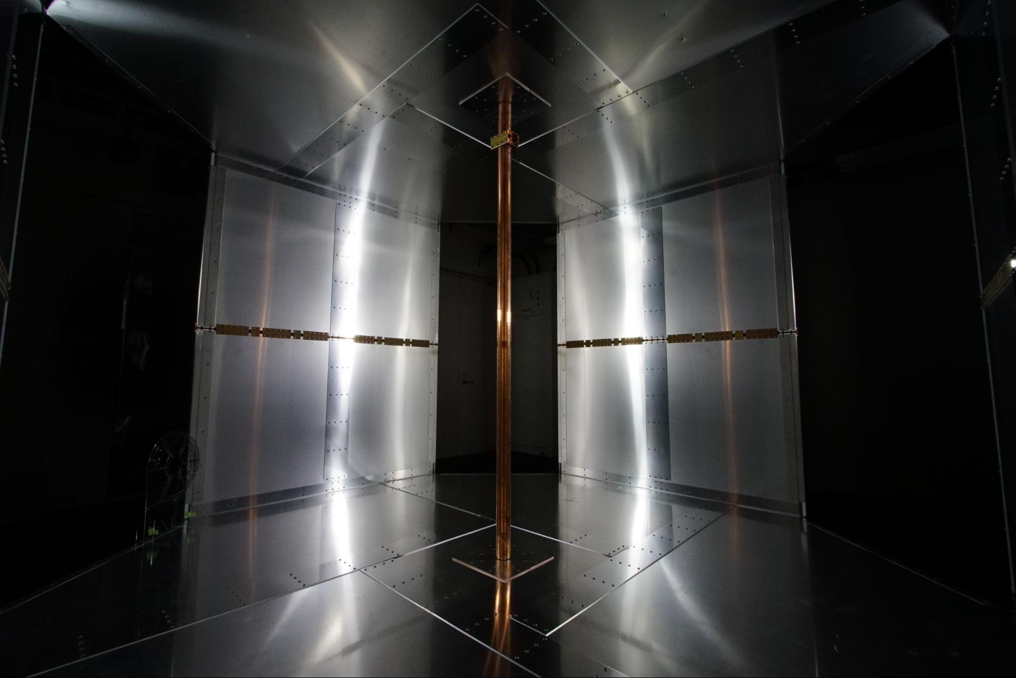 The room is dark with lights reflecting off metallic-looking walls embedded with the charging systems