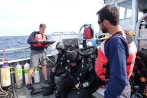 Scuba divers in dry suits prepare to enter the frigid waters of Lake Huron to collect microbial mat samples at the Middle Island Sinkhole in September 2017. Temperatures at the bottom of the sinkhole, where groundwater rich in sulfur and low in oxygen seeps into the lake bottom, can be in the low 40s Fahrenheit. Photo credit: Jim Erickson, University of Michigan News.