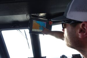 Travis Smith, captain of NOAA's R/V Storm, points to the GPS screen as the boat makes the roughly 90-minute trip from Alpena to the Middle Island Sinkhole. Photo credit: Jim Erickson, University of Michigan News.