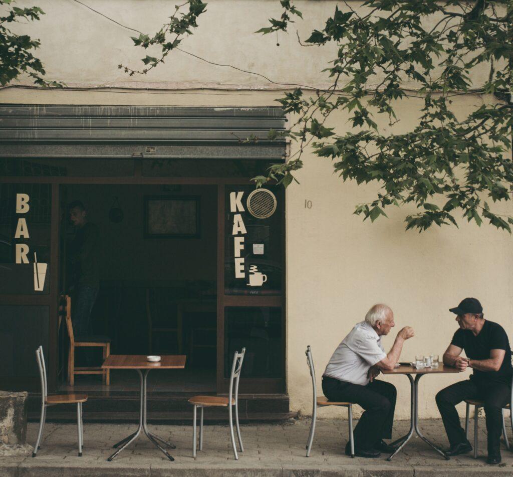 Two men talking at a cafe. Image credit: Juri Gianfrancesco, Unsplash.com