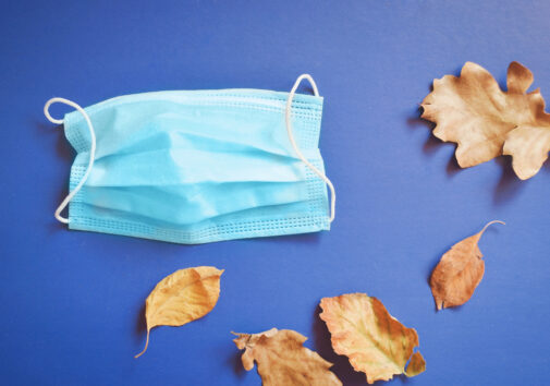 Second wave of coronavirus in autumn and winter. Blue disposable medical mask and yellow leaves. Image credit: leares, iStock