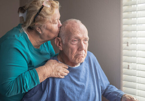 Senior couple kiss forehead window. Image credit: Getty Images