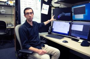 Samuel Nason, a PhD student in biomedical engineering at the University of Michigan, is a member of a research team that has captured brain signals capable of controlling individual finger movements in primates. Image credit: Marcin Szczepanski/University of Michigan Engineering