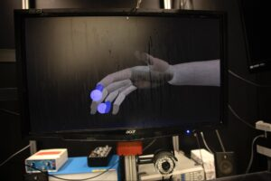 University of Michigan researchers used a computer-generated hand to mirror the motions of the monkeys as they reached for the animated dots—providing data that the team used to train their algorithm for interpreting brain signals. Image credit: Marcin Szczepanski/University of Michigan Engineering