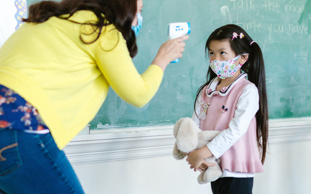Teacher and child masked temperature check.